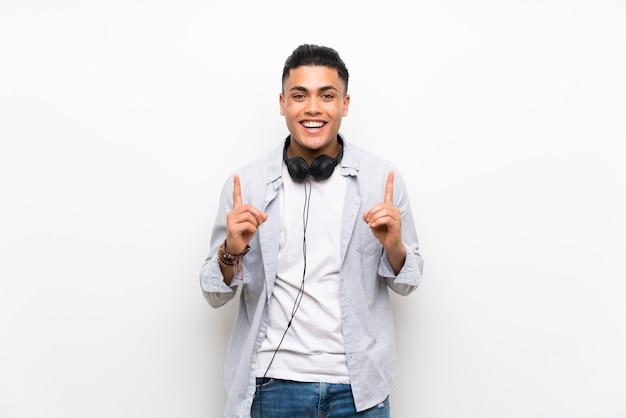Jeune homme sur un mur blanc isolé avec des écouteurs pointant vers le haut une excellente idée