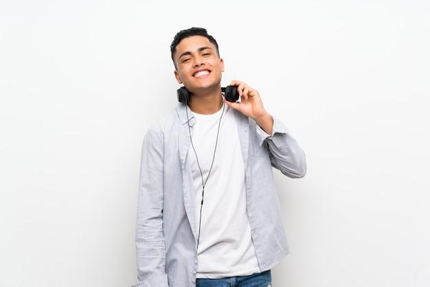Jeune homme sur un mur blanc isolé avec des écouteurs