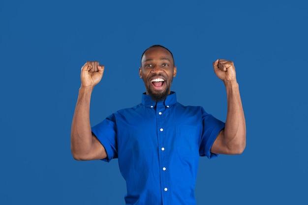 Jeune homme sur le mur bleu du studio