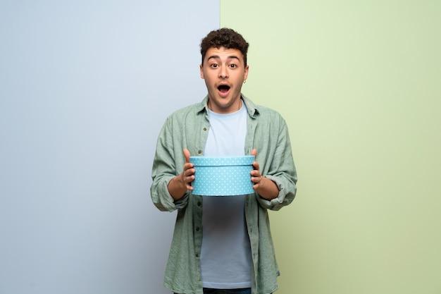 Jeune homme sur un mur bleu et vert surpris parce qu'un cadeau lui a été offert