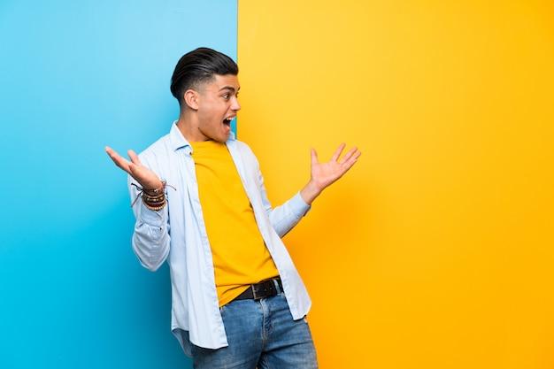 Jeune homme sur un mur coloré isolé avec une expression faciale surprise