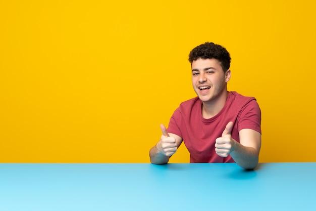Jeune homme avec mur coloré et une table pointant vers l'avant et souriant