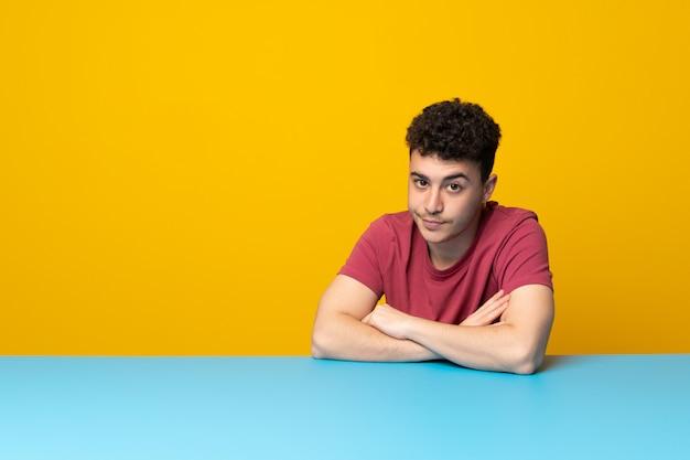 Jeune homme avec mur coloré et table se sentir contrarié