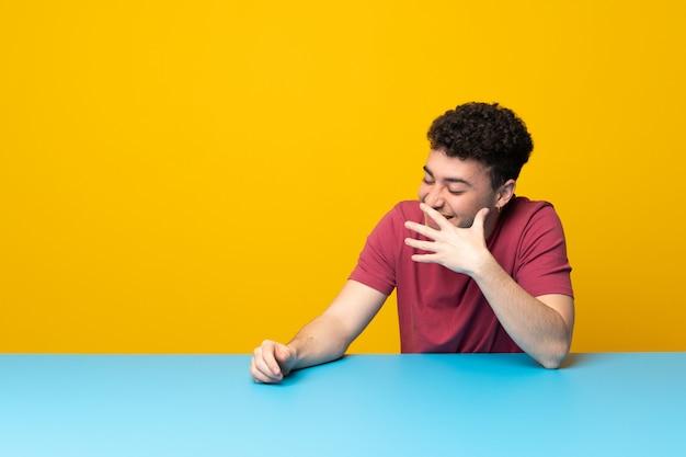 Jeune homme avec mur coloré et table souriant beaucoup