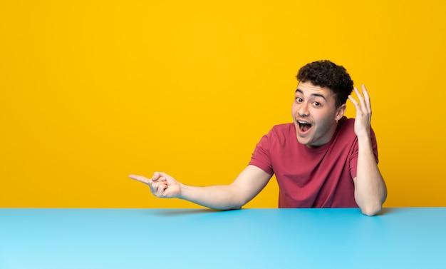 Jeune homme avec mur coloré et table surpris et un doigt pointé sur le côté