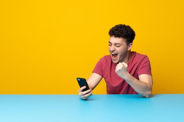 Jeune homme avec mur coloré et table avec téléphone en position de victoire