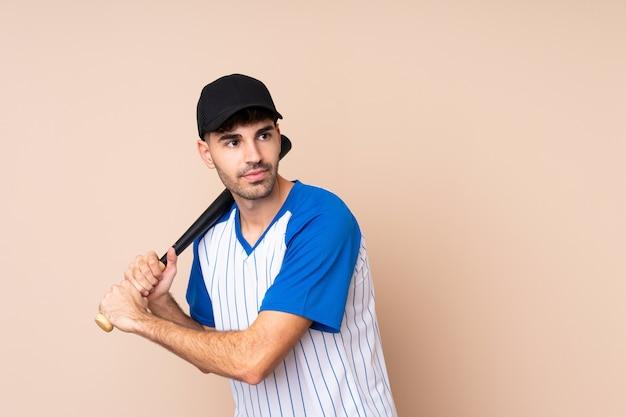 Jeune homme sur mur isolé jouant au baseball