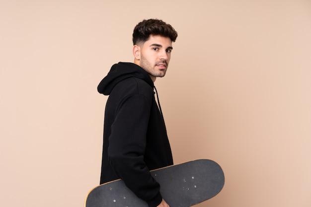 Jeune homme sur un mur isolé avec un patin