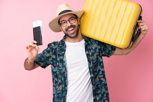 Jeune homme sur un mur isolé en vacances avec valise et passeport
