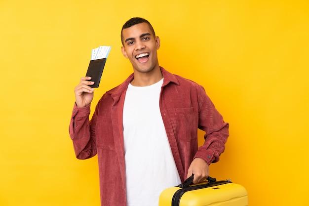 Jeune homme sur un mur jaune isolé en vacances avec valise et passeport