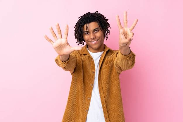 Jeune homme sur mur rose isolé