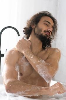 Jeune homme musclé aux yeux fermés lave son corps tout en profitant d'un bain avec de l'eau chaude et de la mousse