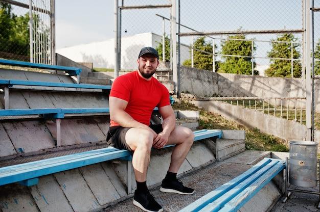 Jeune homme musclé barbu porter sur une chemise rouge, un short et une casquette au stade