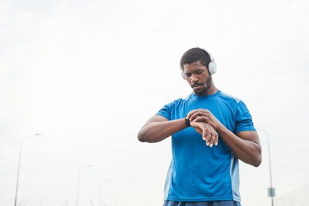 Jeune homme musclé dans des écouteurs sans fil à l'aide d'un bracelet de remise en forme pendant l'entraînement sportif à l'extérieur