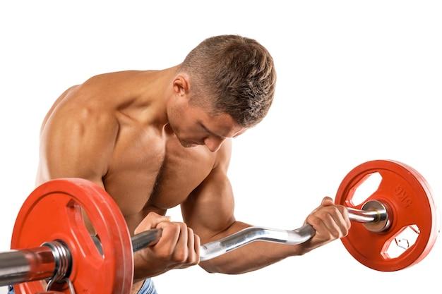Jeune homme musclé faisant exercice de curl haltères biceps sur mur blanc