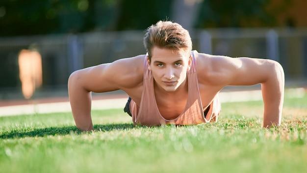 Jeune homme musclé faisant des push ups sur le stade