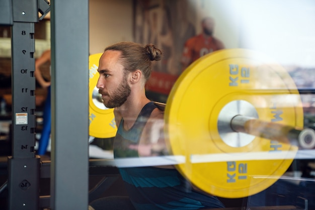 Jeune homme musclé en forme pendant l'entraînement dans la salle de sport