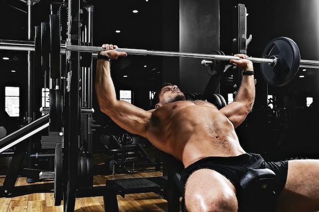 Jeune homme musclé, soulevant un développé couché haltères dans la salle de gym.