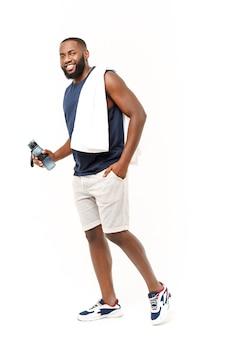 Un jeune homme musclé tient une bouteille d'eau après avoir couru, un athlète attrayant se reposant après une séance d'entraînement à l'extérieur, un concept de remise en forme et de mode de vie sain. isolé sur blanc.