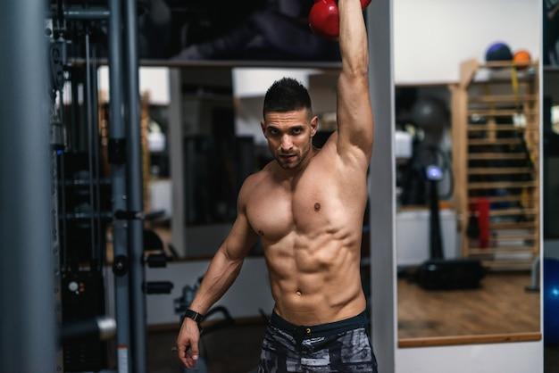 Jeune homme musclé torse nu aux cheveux courts, faire des exercices avec bouilloire-bell
