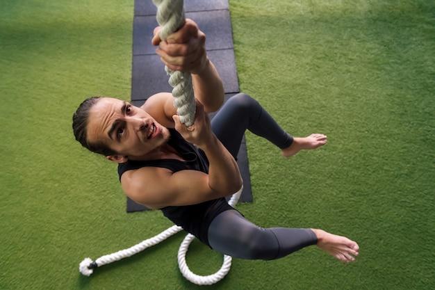 Jeune homme musculation en escaladant une corde