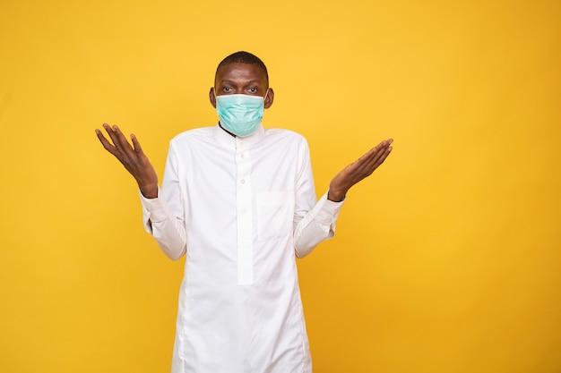 Jeune homme musulman africain portant un masque facial, haussant les épaules