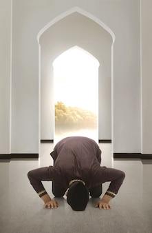 Jeune homme musulman asiah avec capuchon en prière