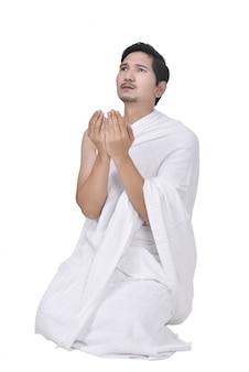 Jeune homme musulman asiatique avec un tissu ihram à genoux et priant