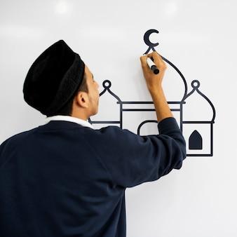 Jeune homme musulman dessinant une mosquée sur un tableau blanc