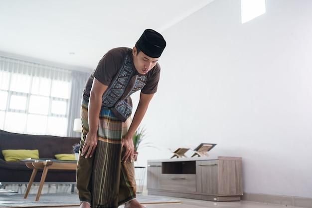 Jeune homme musulman priant à la maison geste rukuk