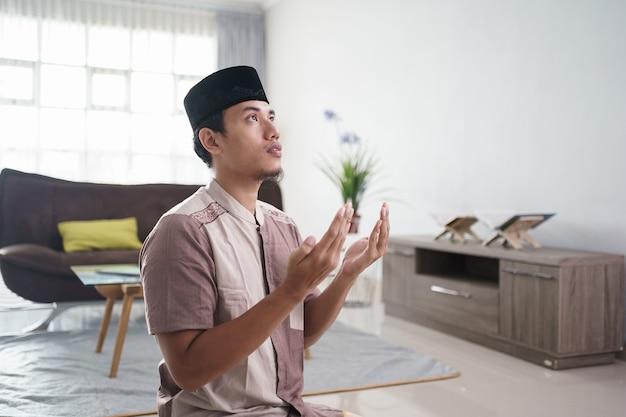 Jeune homme musulman priant à la maison ouvrir son bras pour demander pardon à dieu