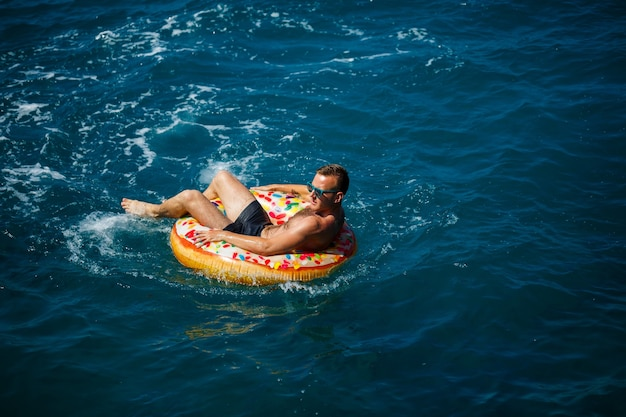 Un jeune homme nage en pleine mer sur un anneau gonflable par une journée ensoleillée. vacances d'été, touriste en vacances