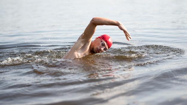 Jeune homme nageant dans le lac