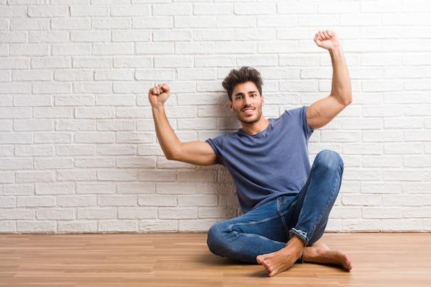 Jeune homme naturel assis sur un plancher en bois très heureux et excité, levant les bras