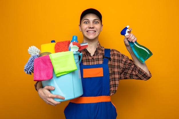 Jeune homme de nettoyage excité portant un uniforme et une casquette tenant un seau d'outils de nettoyage avec un agent de nettoyage