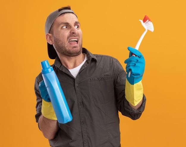 Jeune homme de nettoyage portant des vêtements décontractés et capuchon dans des gants en caoutchouc tenant une brosse de nettoyage et une bouteille avec des produits de nettoyage à la mécontentement avec une expression digérée debout sur un mur orange