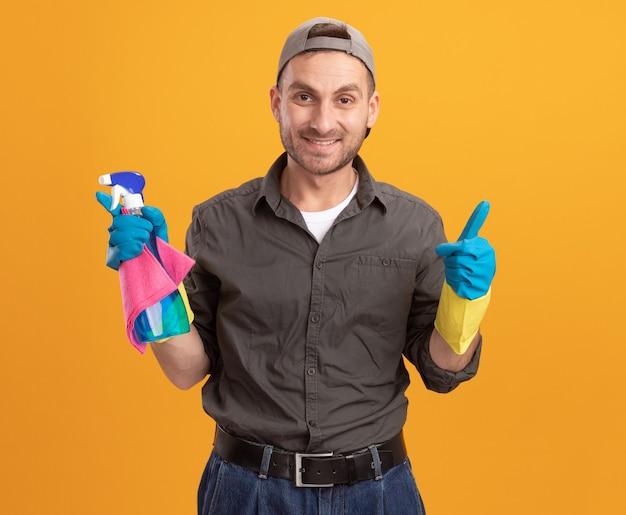 Jeune homme de nettoyage portant des vêtements décontractés et une casquette dans des gants en caoutchouc tenant un flacon pulvérisateur et un chiffon à sourire joyeusement showign pouces debout sur le mur orange
