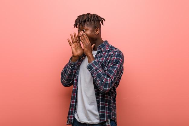 Un jeune homme noir africain crie fort, garde les yeux ouverts et les mains tendues.