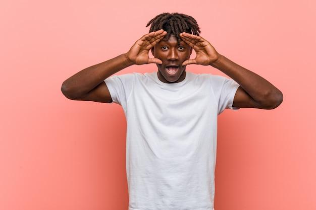 Jeune homme noir africain en gardant les yeux ouverts pour trouver une opportunité de réussite.