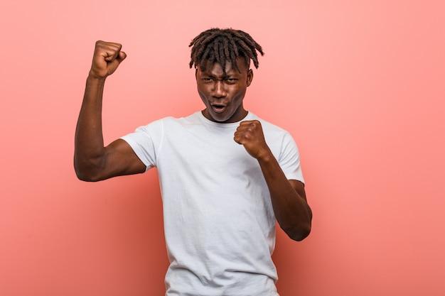 Jeune homme noir africain, levant le poing après une victoire, concept gagnant.