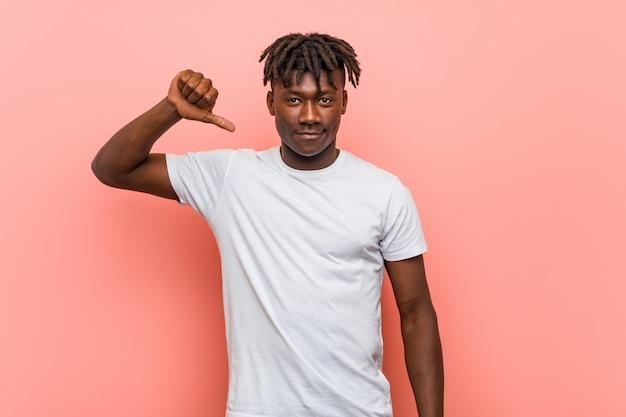 Jeune homme noir africain montrant un geste d'aversion, les pouces vers le bas. concept de désaccord.