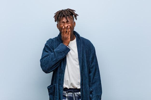 Jeune homme noir africain portant un pyjama bâillant montrant un geste fatigué couvrant la bouche avec sa main.