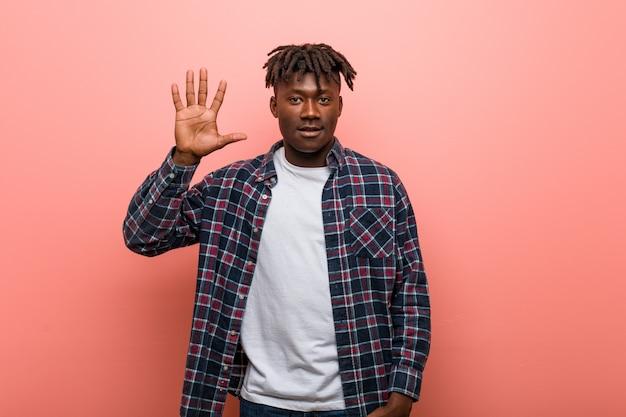 Jeune homme noir africain souriant souriant montrant le numéro cinq avec les doigts.