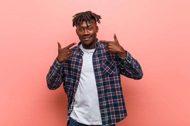 Jeune homme noir africain sourit, pointer du doigt la bouche.