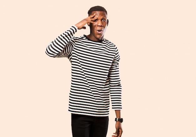 Jeune homme noir afro-américain à l'air heureux, étonné et surpris, souriant et réalisant de bonnes et incroyables bonnes nouvelles contre le mur beige