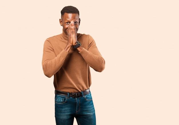 Jeune homme noir afro-américain à la bouche heureuse, gaie, chanceuse et surprise couvrant les deux mains sur le mur beige