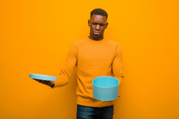 Jeune homme noir afro-américain contre le mur orange avec un cadeau