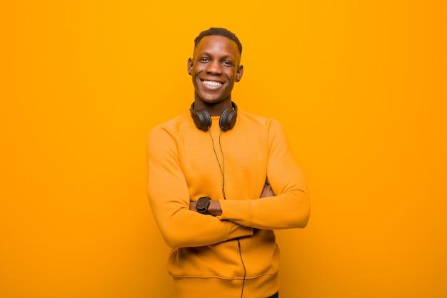 Jeune homme noir afro-américain contre le mur orange avec un casque