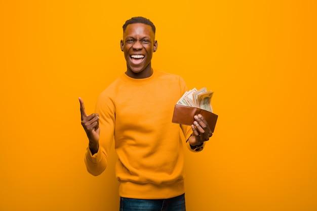 Jeune homme noir afro-américain contre le mur orange, le concept de l'argent.
