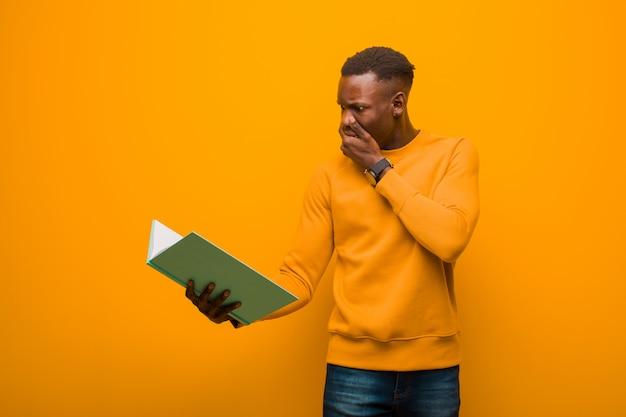 Jeune homme noir afro-américain contre le mur orange avec un livre